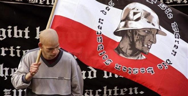 Un seguidor del partido neonazi alemá NPD sujeta una bandera durante una concentración
