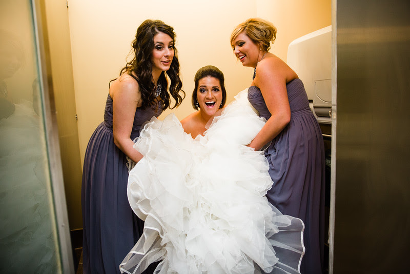 The bride gets help from her bridesmaids at Prairie Street Brewhouse when she really has to go to the bathroom at her wedding reception!