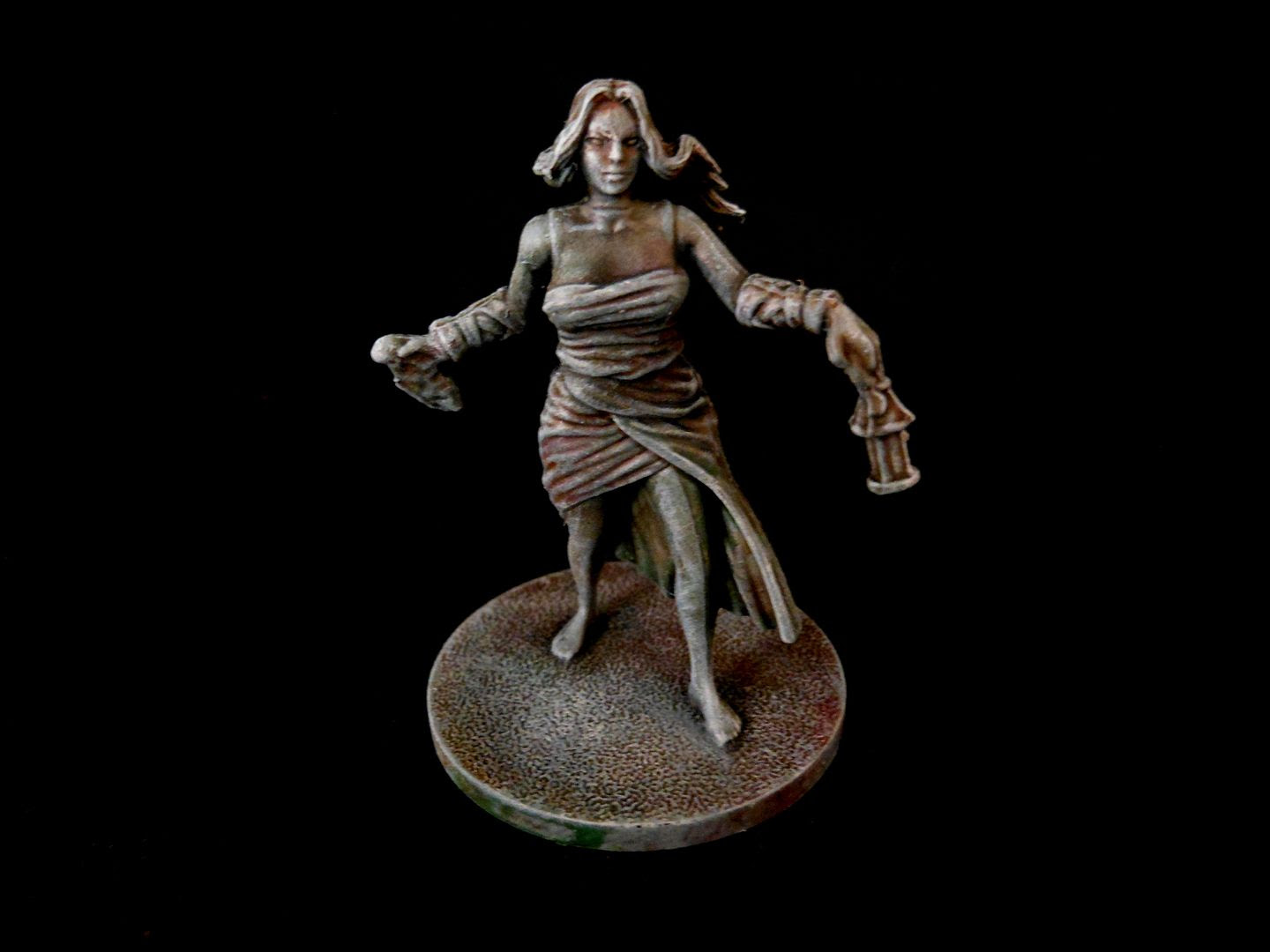 A female survivor from Kingdom Death: Monster, painted to look like stone.