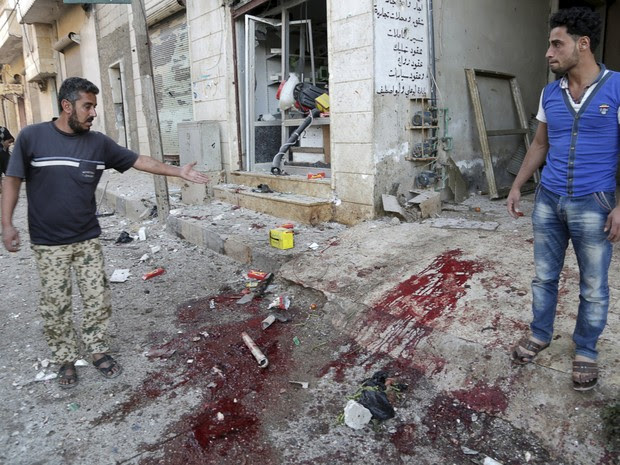 Sírios indicam manchas de sangue em região bombardeada em Jabal al-Zawiya (Foto: Reuters/Khalil Ashawi)