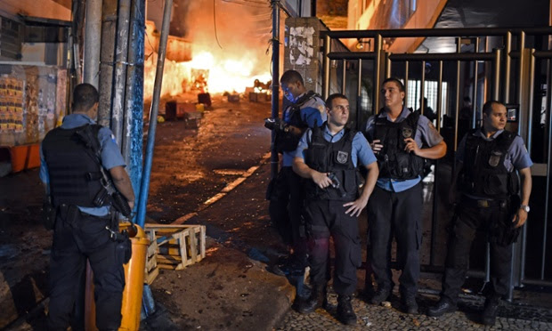 Rio de Janeiro's state military policemen stand in position during a violent protest in a favela next to Copacabana, Rio de Janeiro as protests broke out following the death of a resident last weekend during clashes with the Army in a nearby favela.