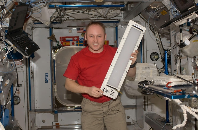 Astronaut Mike Fincke holds a light fixture inside of Node 2 on the International Space Station. The fluorescent-based lights currently on ISS will soon be replaced by a customized, dynamic LED system, which NASA-funded Behavioral Health and Performance researchers will evaluate in their upcoming flight experiment.