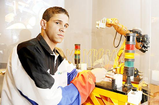 O instrutor do Senai em Alagoas Darilton de Lima Pinheiro, 22, com a réplica do robô Kuka KR-16 que ganhou de prêmio
