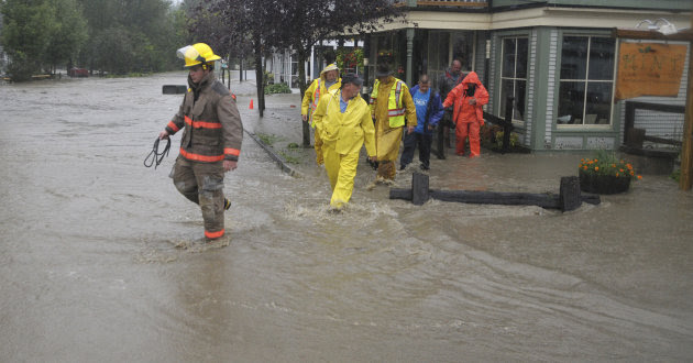 Waitsfield firefighters and rescuers wade through a street flooded by rain from Tropical Storm Irene after assisting residents in a building in Waitsfield, Vt., Sunday, Aug. 28, 2011. (AP Photo/Sandy