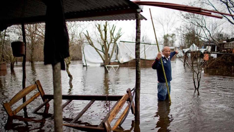 Carlos Galiano señala  en dirección de su casa mientras vadea a través de un área inundada en Olivera Provincia de Buenos Aires. (Natacha Pisarenko / AP)