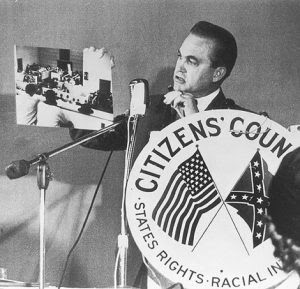 """Alabama Governor George Wallace, holding photograph of alleged """"known agitators"""", while speaking to Citizens' Council group in Atlanta in 1963. Library of Congress."""