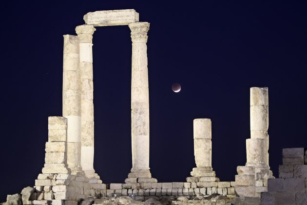 A partial lunar eclipse is seen from the Roman pillars of the Temple of Hercules in Amman
