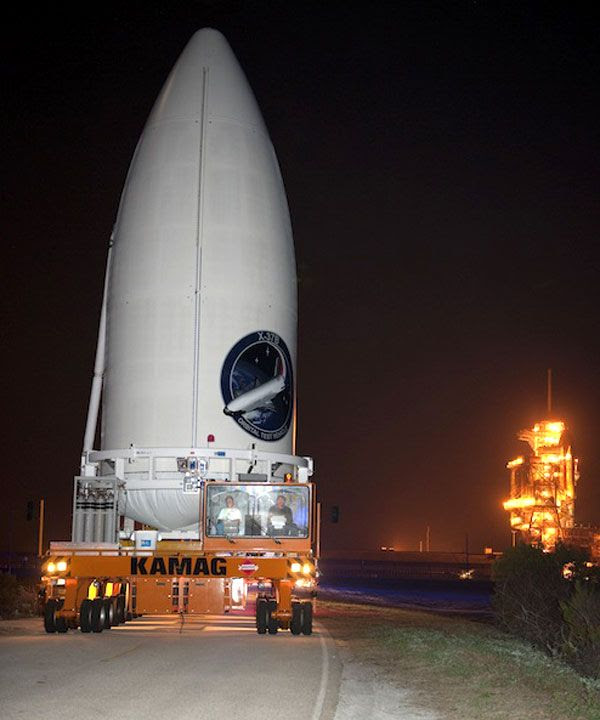 With space shuttle Discovery in the background, the Atlas V payload fairing carrying the OTV is transported to its launch pad, ahead of its March 2011 liftoff from Cape Canaveral Air Force Station in Florida.