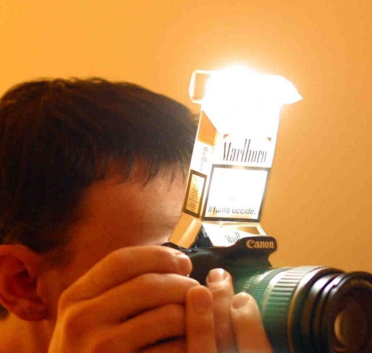Chico utilizando una cajetilla de cigarros como difusor de luz de un flash para su cámara profesional
