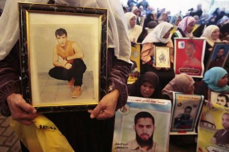 Palestinos muestran imágenes de varios presos durante una protesta en Gaza. | Reuters