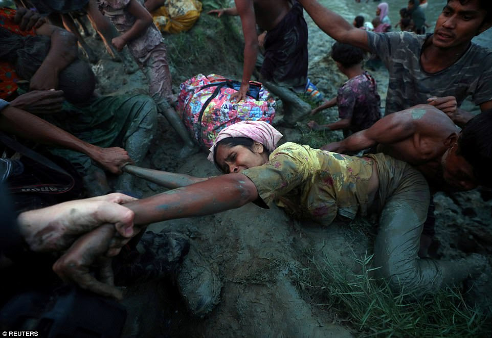 Photographers help a Rohingya refugee to come out of Naf River as they cross the Myanmar-Bangladesh border in Palong Khali, near Cox's Bazar, Bangladesh, on November 1