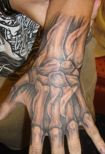 Tattoo of bones in the hand. Here is a way to stay down with Halloween year