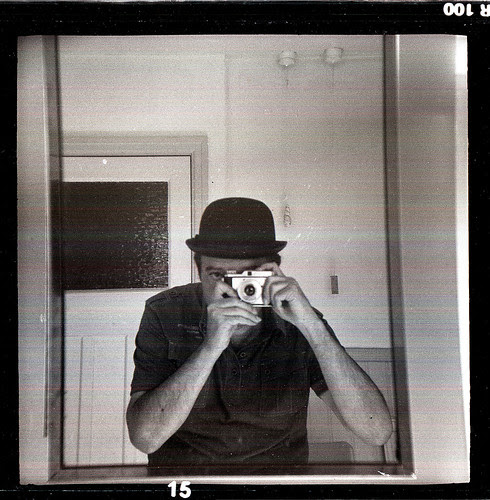reflected self-portrait with Luxette camera and bowler hat by pho-Tony