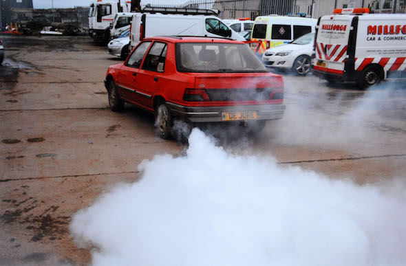 """A speeding driver who deployed a James Bond-style smokescreen device in a bid to shake off police has been spared jail.  Simon Chaplin, 62, rigged a bucket of diesel, a pump and pipes, behind the passenger seat of his Peugeot 309 to produce """"colossal"""" amounts of grey smoke from his exhaust.  A court heard """"eccentric"""" Chaplin activated the device when a policeman attempted to pull him over for speeding and covered the carriageway with fumes.  Chaplin tried to evade the officer's flashing blue lights but the policeman was simply able to follow the billowing plumes through country roads near Haverfordwest, Pembs.   Pictured here is the smokescreen in action  © WALES NEWS SERVICE"""
