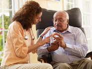 Woman showing an elderly man a medicine bottle