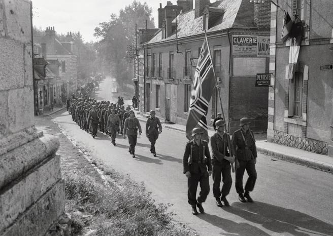 Soldados nazis derrotados pasan por delante de un edificio donde cuelga la bandera de la ONU en Veaugency