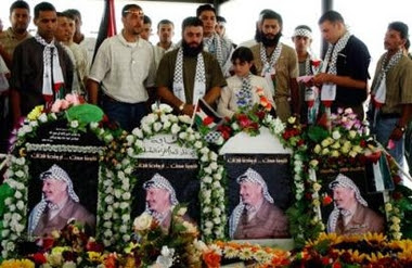 Palestinian former prisoners pay their respects at the grave of the late Palestinian leader Yasser Arafat at his former headquarters in the West Bank city of Ramallah, Thursday June 2, 2005.
