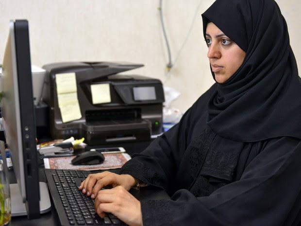 Nassima al-Sadah, candidata a uma vaga no conselho municipal de Qatif, é vista trabalhando em seu escritório, na quinta (26) (Foto: AFP Photo/STR)