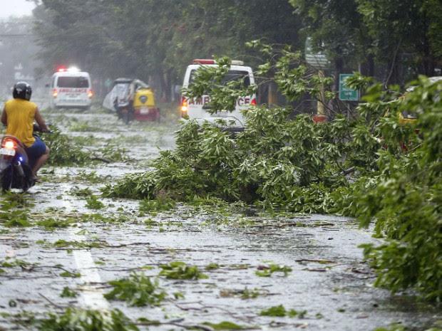 Veículo atravessa estrada repleto de pedaços de árvores que caíram em Manila, nas Filipinas (Foto: Erik De Castro/Reuters)