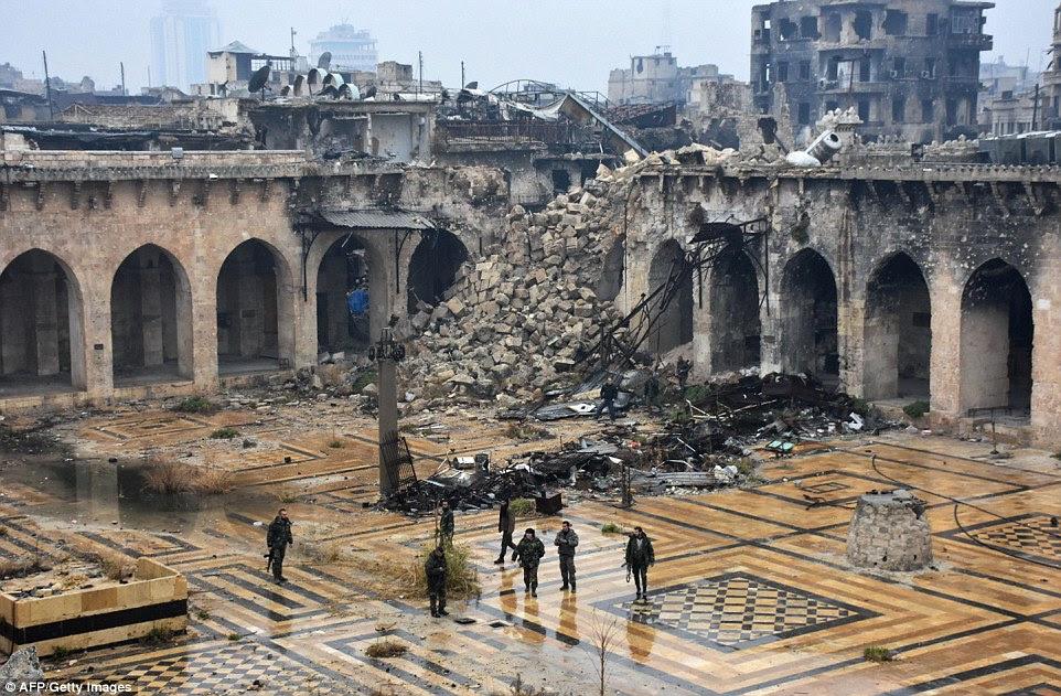 forças pró-governo sírio pé na antiga mesquita Umayyad na cidade velha de Aleppo, que agora está em ruínas