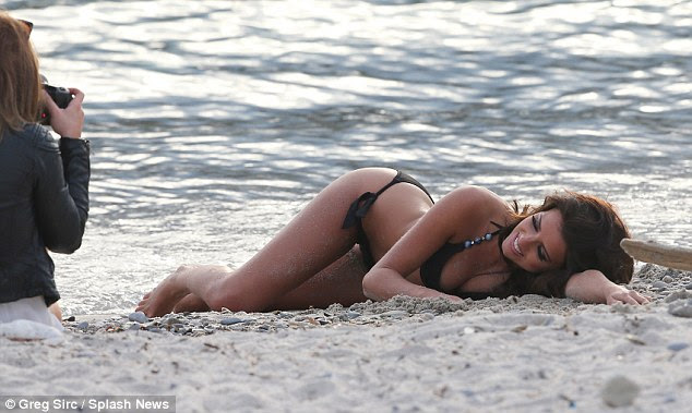 True professional: The reality star seemed to get an attack of the giggles as she reclined on the white sand