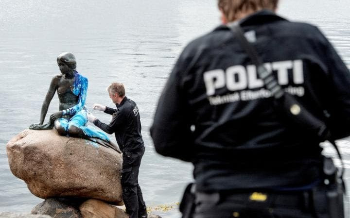 Police officers inspect the Little Mermaid statue, seen covered in paint, for the second time in weeks, in what local authorities say is an act of vandalism, in Copenhagen.