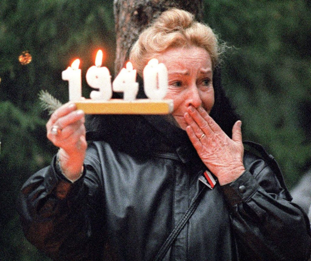 KATYN, RUSSIA - OCTOBER 31: A Polish woman holds a commemorative candle in Katyn 31 October 1989, as she mourns Polish officers killed by NKWD (Stalin's secret police) in the forest of Katyn, in 1940. Families of the murdered Polish officers were allowed access to the symbolic tomb in Russia. (Photo credit should read WOJTEK DRUSZCZ/AFP/Getty Images)