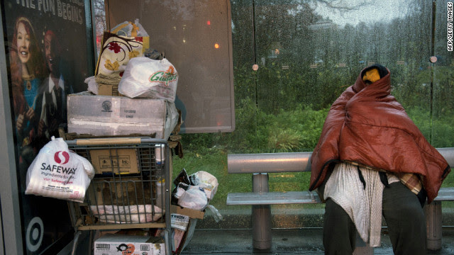 John Edgecombe II, who is homeless, takes refuge from the rain and wind at a bus stop in Ward Circle in Washington on Monday.