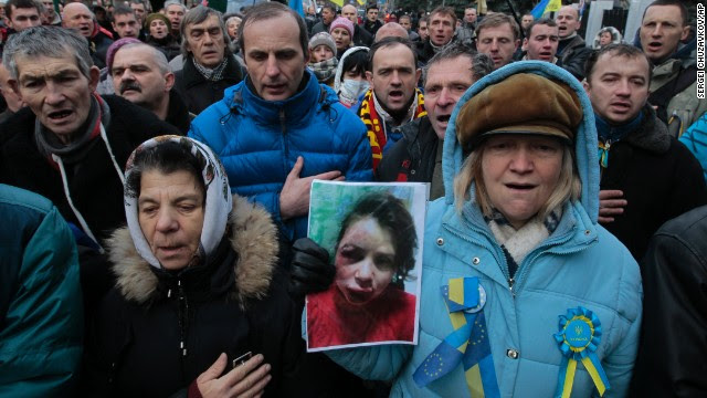 Activists outside the Ukrainian Interior Ministry in Kiev, hold a photo showing the injuries to journalist Tetiana Chornovol.