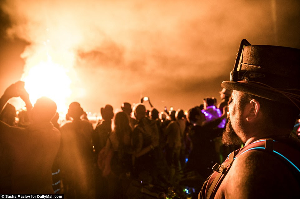 Lights from the flames reflect off festival goers stood in the Nevada desert
