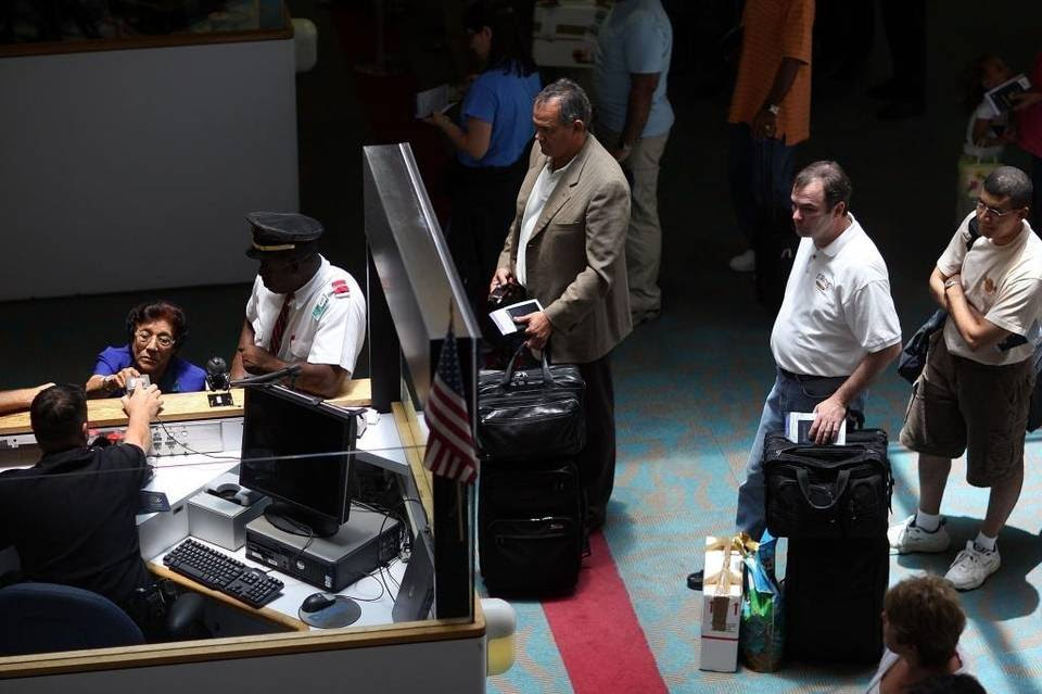 A Customs and Border Protection (CBP) officer at Miami International Airport (MIA) checks the passports of international travelers.