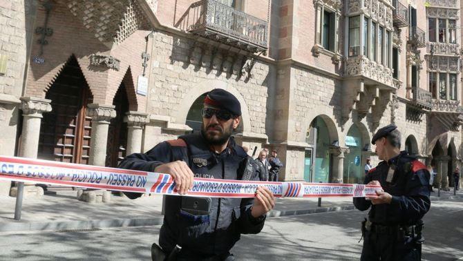 Dos mossos acordonant els voltants de la Casa de les Punxes, on hi ha la seu del Diplocat, escorcollat per la Guàrdia Civil (ACN)