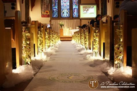 Lighted aisle decorations, vases filled with water and
