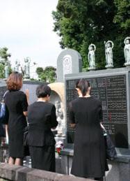 法要の後、永代供養墓にお参りをする遺族。遺骨は骨つぼで安置されている(東京・広尾の東江寺)