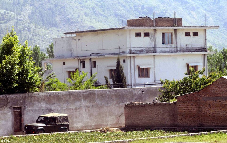 Pakistani Army soldiers pass by the compound where Osama Bin Laden was killed by US military forces