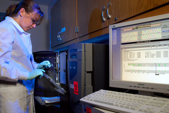 CDC Scientist using new AMD technology to study samples. A computer screen in the foreground shows data from this testing.