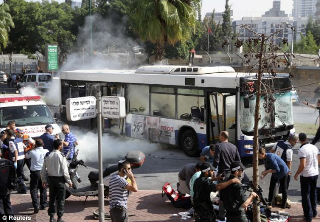 A wounded woman is treated on the ground as smoke rises from the bus earlier today