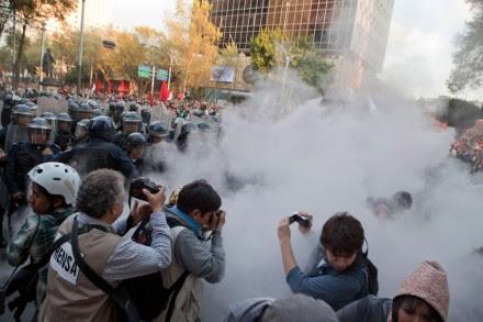 Reporteros corren del gas lacrimógeno durante la marcha a 45 años de la matanza de Tlatelolco. Foto: Miguel Dimayuga