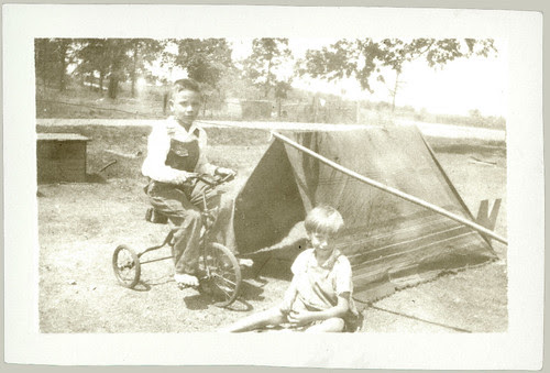 Two children, tent and tricycle