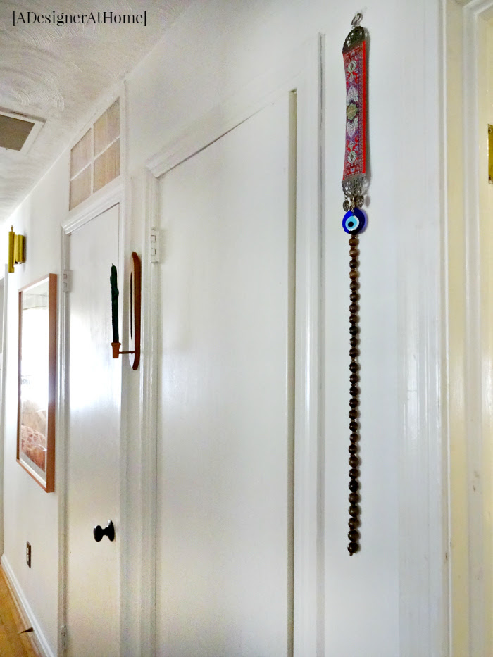 simple thrifted and handmade treasures don the walls of this hallway