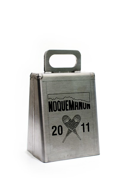 A metal cowbell with the Noquemanon logo