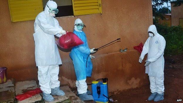 Os profissionais de saúde tiram suas roupas de proteção depois de terminar áreas de desinfecção em um hospital de Pita, Guiné - 25 de agosto de 2014