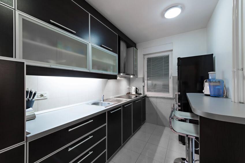 Petite cuisine avec armoires noires partout.