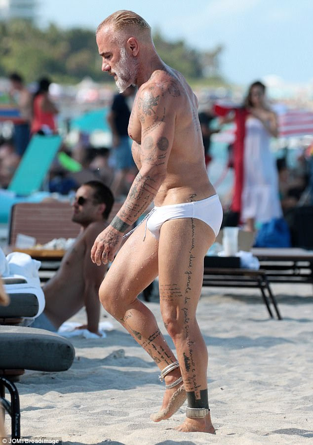 Proud: Showcasing his buff physique, which is scattered with tattoos, the Italian millionaire seemed to be in high spirits as he took a dip in the sea
