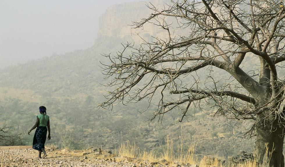 Una mujer camina por una zona desértica en Mali.