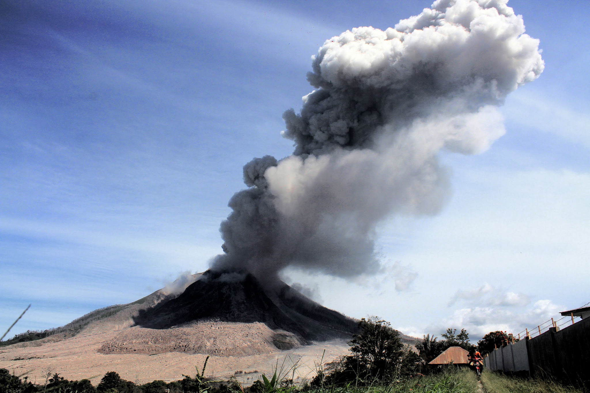 Mount Sinabung volcano spews volcanic ash into the air as seen from the Karo district in North Sumatra province, on May 25, 2016. Indonesian rescuers searched for survivors in scorched villages and devastated farmlands on May 23 after the volcano erupted in clouds of searing ash and gas, killing seven and leaving others fighting life-threatening burns. / AFP PHOTO / GATHA GINTINGGATHA GINTING/AFP/Getty Images
