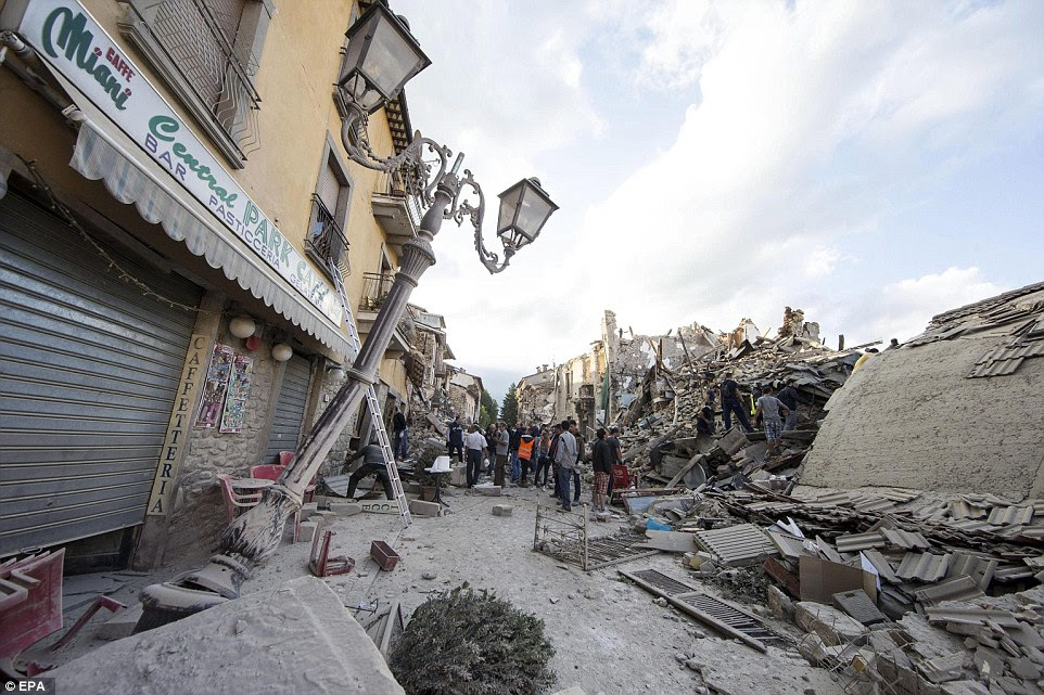 Ruins: A lamppost is seen leaning dramatically to one side next to a devastated building and rescue workers
