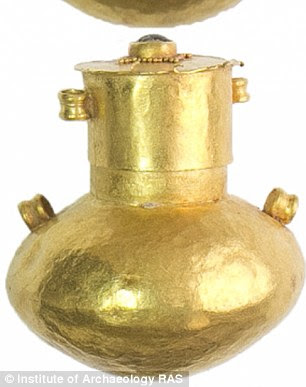 Next to her skull were found gold earrings with pendant chains (pictured, right), while a bronze mirror was close to her shoulder and at her pelvis lay a gold vial (pictured, left)