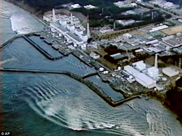This aerial photograph shows the moment went the tsunami, which struck on March 11, hit the Fukushima Dai-ichi nuclear power plant