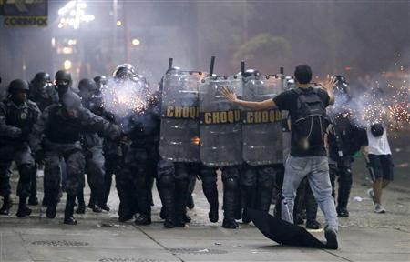 A demonstrator tries to stop the riot police during one of many protests around Brazil's major cities in Rio de Janeiro June 20, 2013. REUTERS-Sergio Moraes